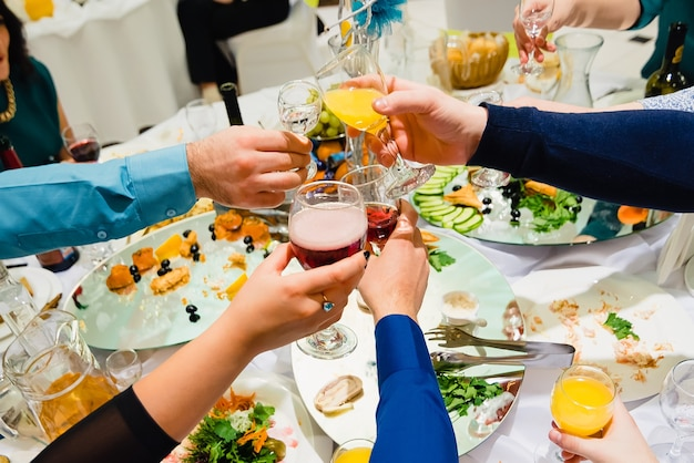 Many hands with different glasses of wine clink and jingle in the holiday