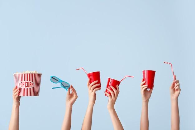 Многие руки с попкорном, напитками и очками на синем