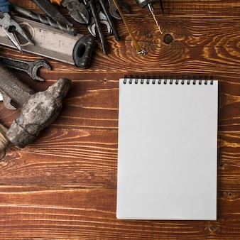 Many handy tools and notebook on wooden table, top view