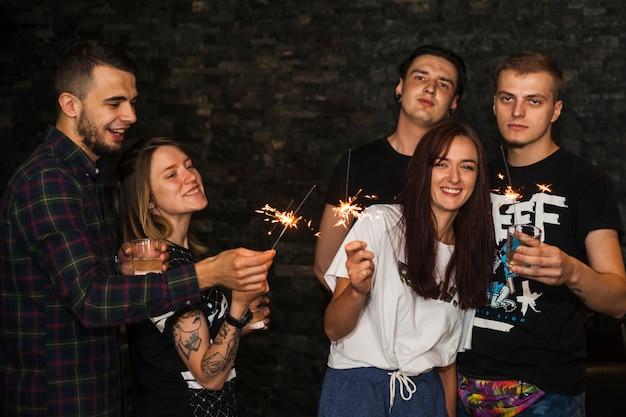 Molti amici felici che tengono scintilla per la celebrazione