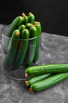 Many harvest cucumbers in vase on the grey concrete background. top view,