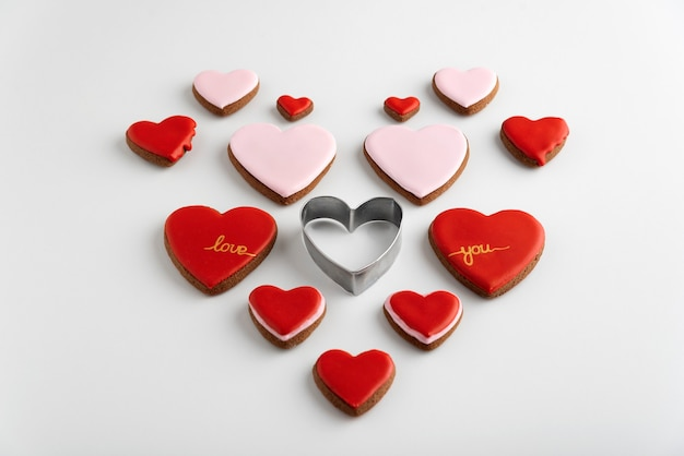 Many heart-shaped cookies with color sugar icing. white background. valentines day treat.
