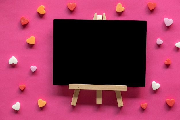 Many hearts around blackboard on pink background, love icon, valentine's day, relationships concept