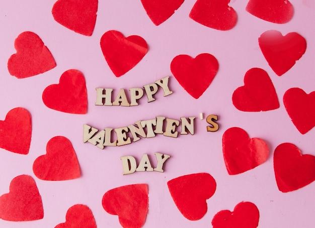 ピンクの背景に幸せなバレンタインデーの碑文を持つ多くの心。