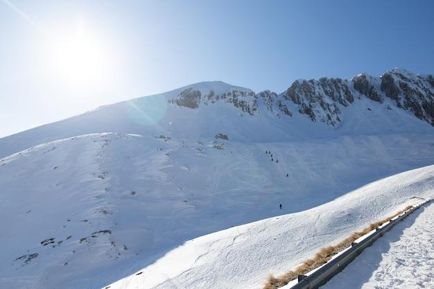 Многие туристы-альпинисты поднимаются на высокую гору. поход по заснеженной горе.