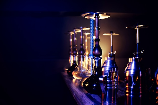 Many hookahs with shisha glass flasks and metal bowls