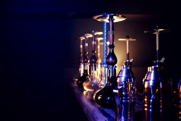 Many hookahs with shisha glass flasks and metal bowls