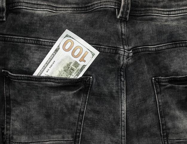 Многие сотни долларовых купюр в кармане джинсов. доллары сша видны в вашем кармане.