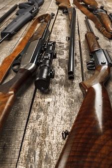Многие охотничьи ружья на выветрившейся деревянной поверхности