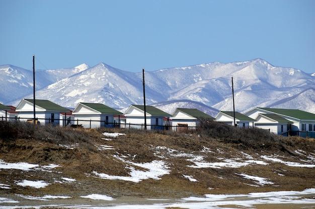 Множество одинаковых домиков для кемпинга и базирования у подножия заснеженных гор.