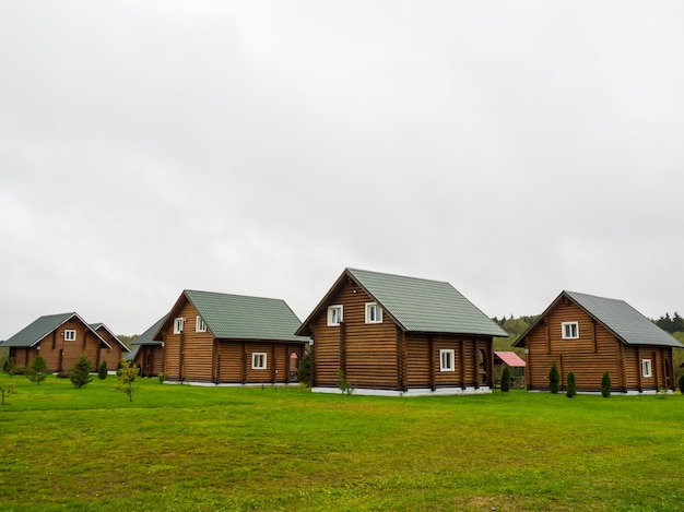 Множество одинаковых больших бревенчатых домов снаружи с засаженным травой задним двором.