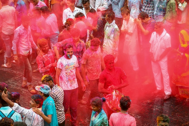 Many indian people celebrating holi festival and spreading red colors in the air
