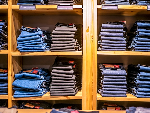 Many jeans laying on the shelf in the clothes store
