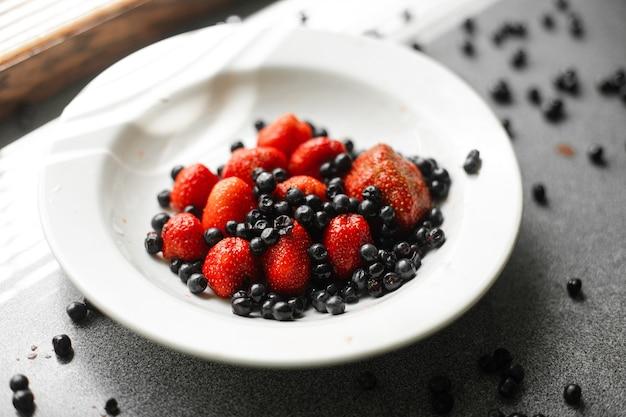 많은 즙이 많고 잘 익은 빨간 딸기와 블랙베리는 밝은 햇빛 아래 탁자 위의 흰색 세라믹 접시에 놓여 있습니다
