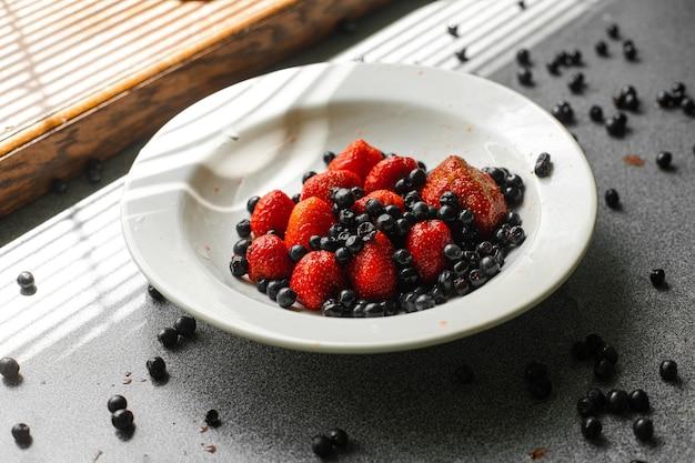 Molte fragole e more rosse mature fresche e succose giacciono su un piatto di ceramica bianca sul tavolo sotto la luce del sole