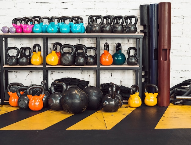 Many kettlebells arranged on rack in fitness club