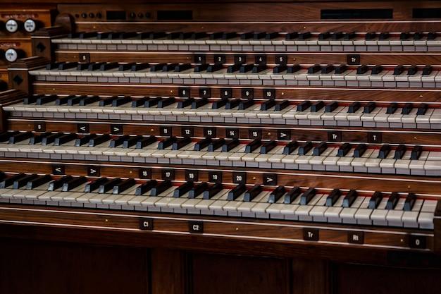 Many keys on a big old brown church organ.