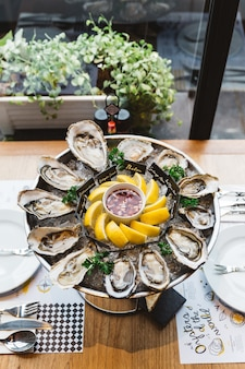 Many kinds of fresh oysters served in round tray with slice lemon and spicy sauce.