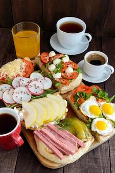 Многие виды бутербродов брускетта и чай кофе свежий сок семейный завтрак