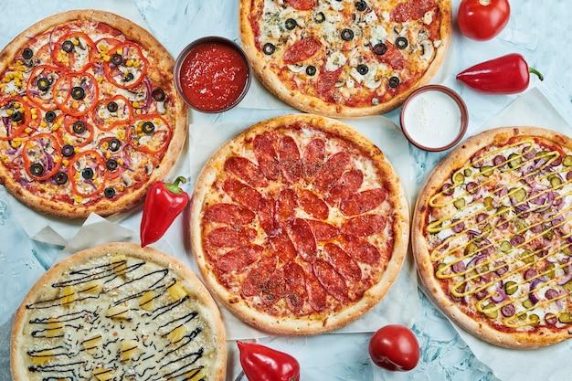 Много видов вкусной пиццы с салями, мясом и курицей на светлом столе. стол со многими итальянской домашней пиццы. плоская кладка еды