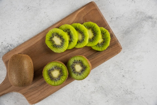 Molte delle fette di frutta kiwi sulla tavola di legno.