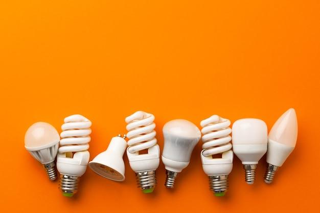 明るいオレンジ色の背景に多くの電球
