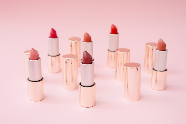 Many luxury gold lipsticks in different shades of pink stand on a pink pastel background
