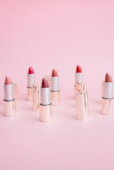 Many luxury gold lipsticks in different shades of pink stand