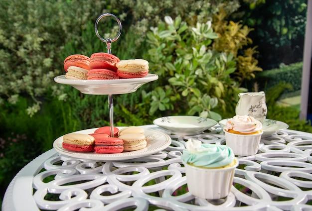 庭にセットされたプレートにピンク、白、カップケーキの多くのマカロン。甘いデザート。コンセプトをリラックスします。
