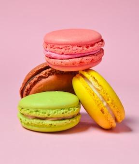 Many macaroons on a pink pastel background. minimalism