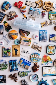 Many magnets on fridge showing different countries with face protection mask