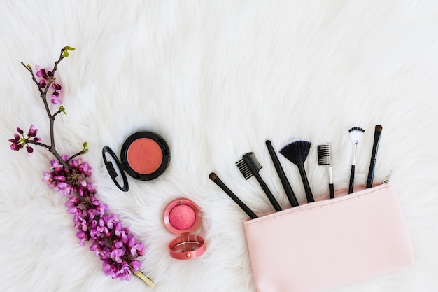 Many makeup brushes out of pink bag; flower twig and compact face powder on soft white fur