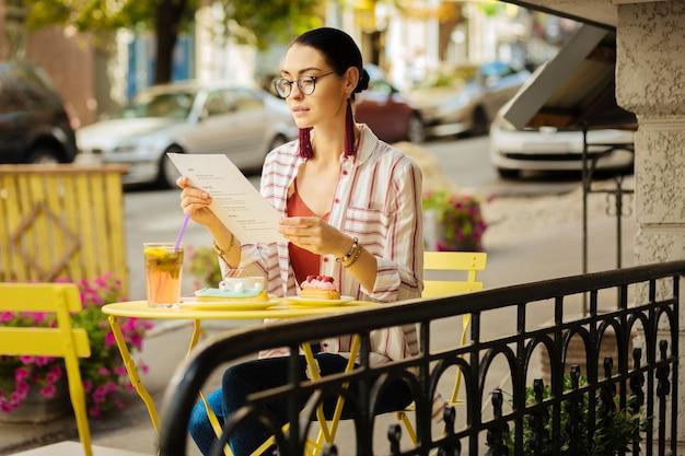 多くの食事。メニューを見て、カフェで美味しいデザートを食べる準備をしている落ち着いた気配りのある女性