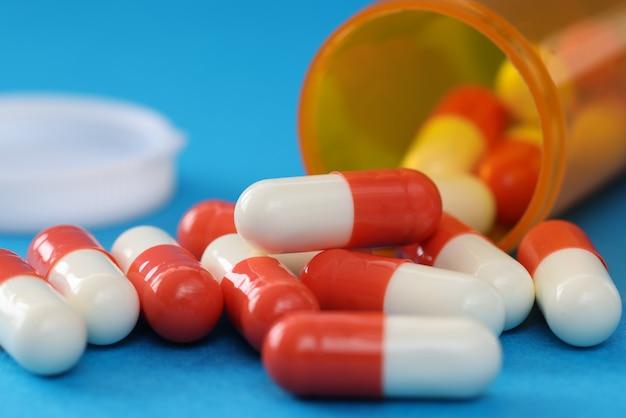 メディシンジャーのクローズアップからこぼれる多くの医療用カプセル。麻薬の概念の過剰摂取