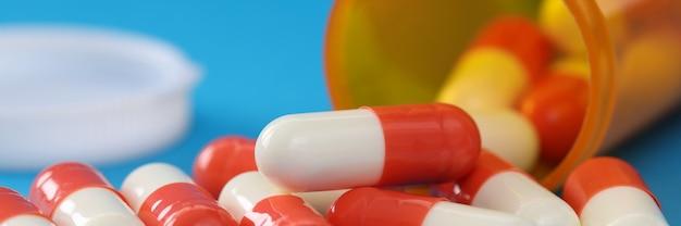 薬瓶のクローズアップからこぼれる多くの医療用カプセル。麻薬の概念の過剰摂取
