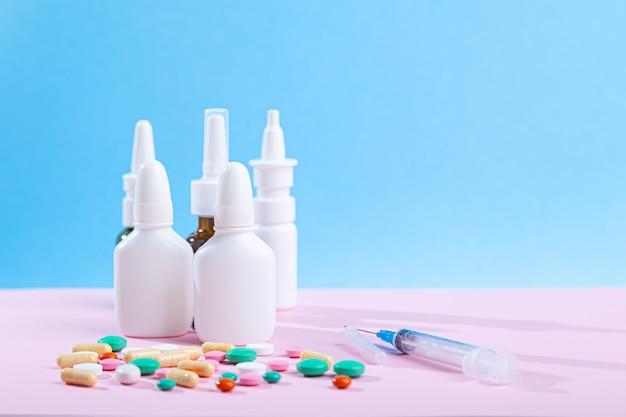 많은 의료 의약품, 주사기, 스프레이, 코 방울 병, 알약 병 다채로운 정제에서 흩어져