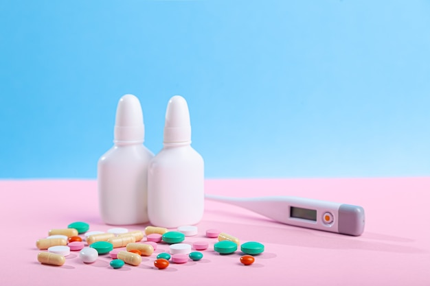 Many medical medicines, thermometer, spray, bottles of nose drops, scattered colored tablets, capsules on blue wall, vitamins, horizontal, copy space, side view