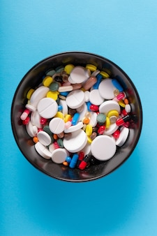 Many medical pills and capsules in a bowl on a blue background, top view