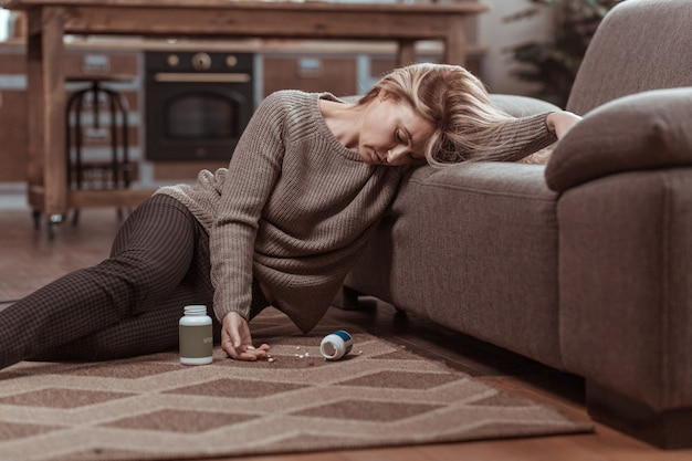 Many meds. blonde woman wearing brown sweater falling on floor after taking too many meds
