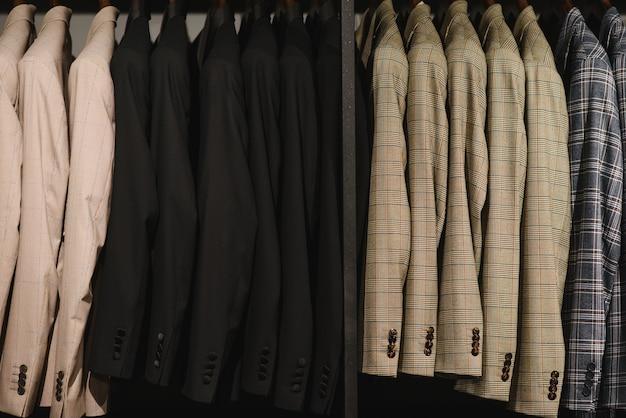 Множество мужских деловых костюмов разных цветов
