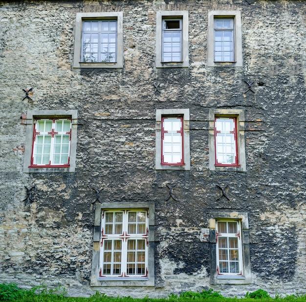 非常に古い中世の家の正面にある多くの散らかった窓。