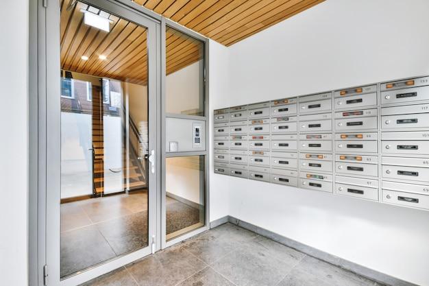 近代的なアパートのガラスのドアの近くの壁に取り付けられた多くの金属製のレターボックス