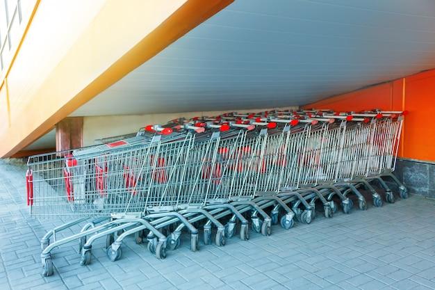 Многие металлические тележки для покупок на стоянке возле супермаркета на открытом воздухе, стоящие под лестницей