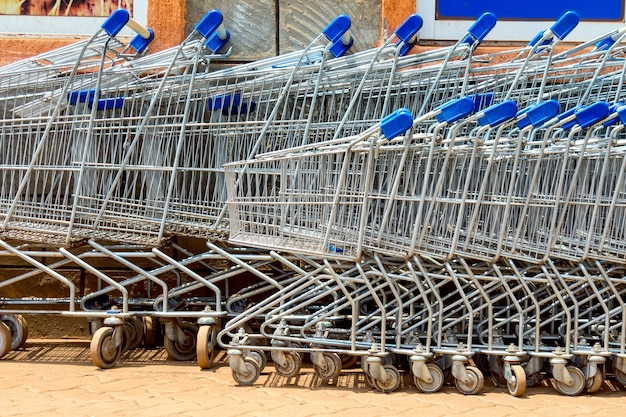 屋外のスーパーマーケット近くの駐車場にある多くの金属製のショッピングカート。
