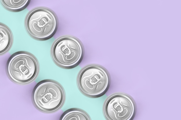 Many metallic beer cans on texture background of fashion pastel
