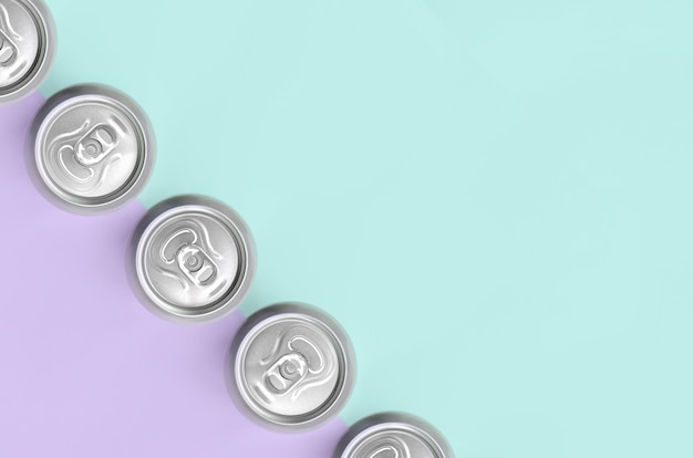 Many metallic beer cans on texture background of fashion