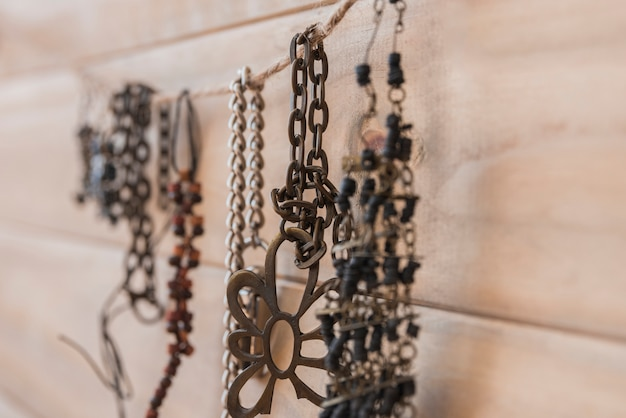 Many metallic bracelets hanging on string against wooden wall