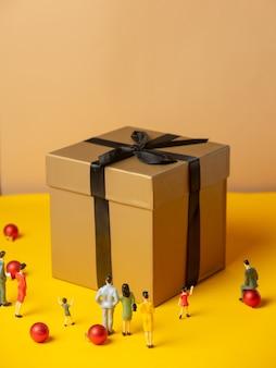 Many miniature figures around christmas gift box on yellow surface