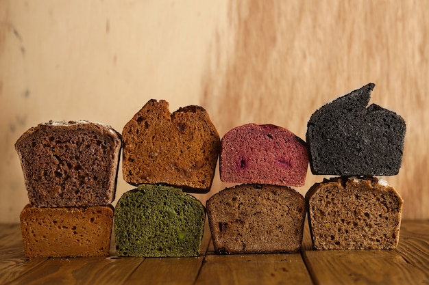 Many mixed alternative baked breads presented as samples for sale on wooden back in professional bakery