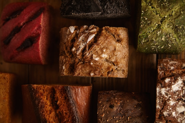 Many mixed alternative baked breads presented for sale on rustic wooden table in professional bakery made from pistachio